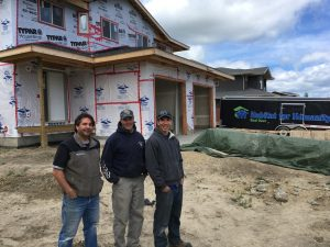 habitat for humanity red deer home build volunteer team in front of home under construction