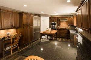 Homestead Custom Carpentry kitchen with dark cabinets, black granite contertops, and stainless steel appliances