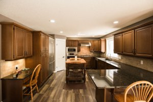 Homestead Custom Carpentry remodeled kitchen with dark wood, black granite countertops, and sleak design