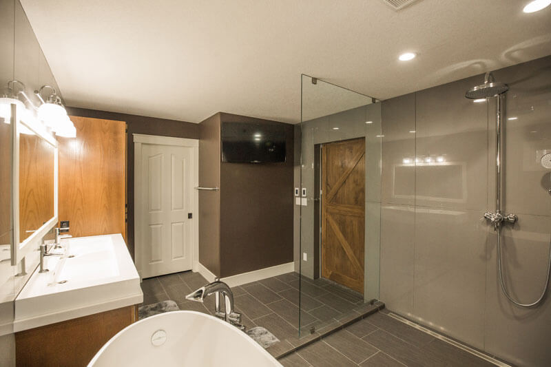 Homestead Custom Carpentry remodeled bathroom with rustic barn door and large showerhead.