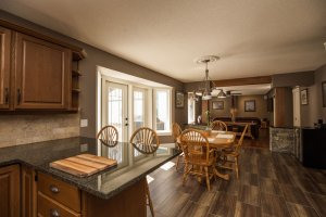 Homestead Custom Carpentry redesigned kitchen and eating area, with dark countertops and cabinets.