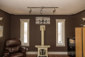 Homestead Custom Carpentry redesigned living space with white woodburning fireplace and natural light windows.