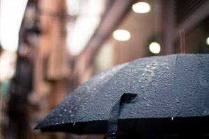 black umbrella outside, covered in rain droplets