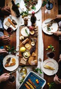 family enjoying an afresco dinner in their backyard on a picnic table